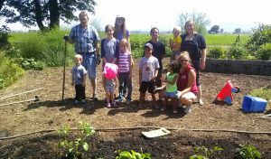 people smiling planting garden beds kids helping out Eugene Lane County oregon