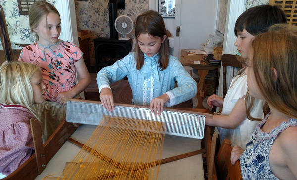 girls working the pioneer loom homeschool
