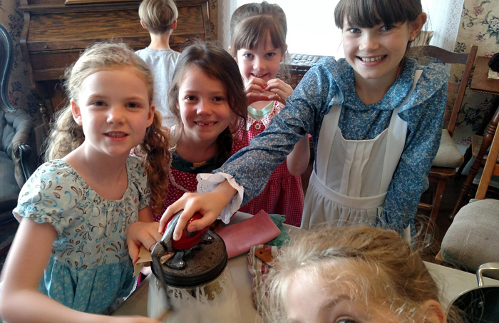kids churning butter homeschool pioneers homesteading