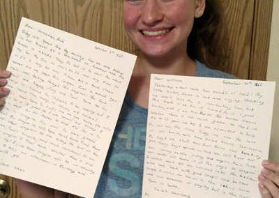 teen with letters from the Oregon Trail presentation singing creek center history