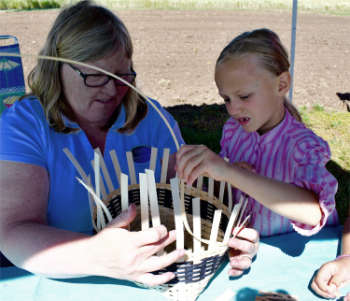 volunteer basket maker with child singing creek educational center